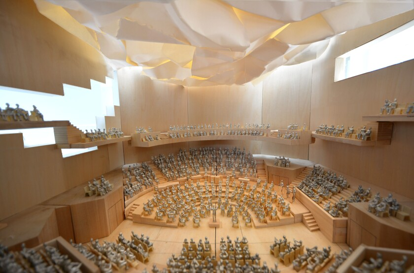 A model shows an interior schematic of concert hall seating under a billowing ceiling