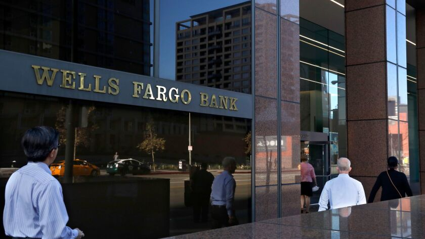 Pedestrians walk past a Wells Fargo bank located at Wells Fargo plaza on 333 S Grand Ave. in downtown Los Angeles on Monday. Wells Fargo stock plunged after the Federal Reserve hit the bank with new sanctions Friday over its fake accounts scandal and other wrongdoing.