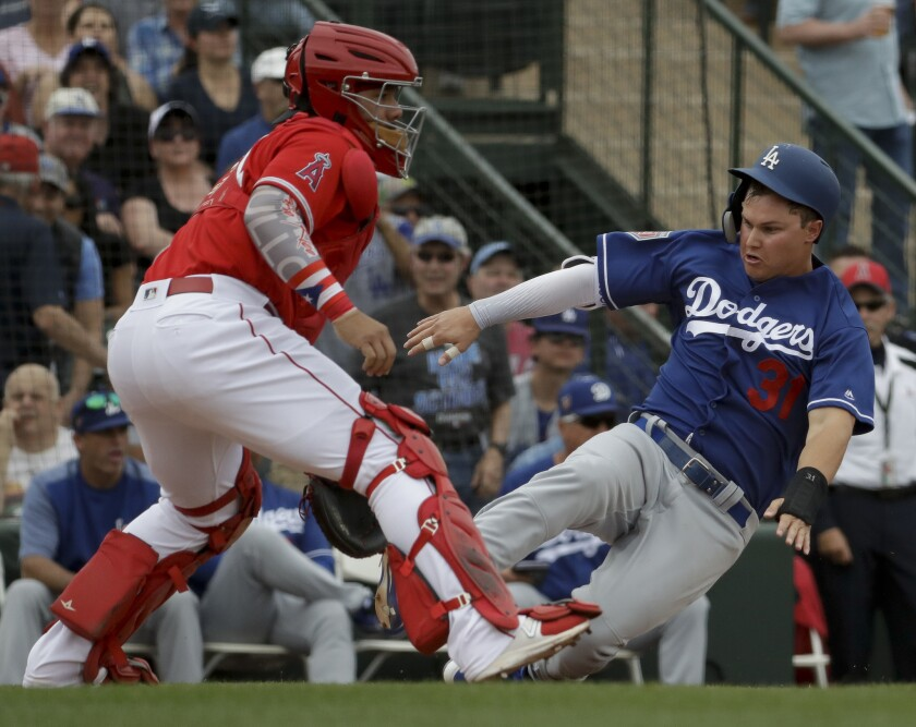 Los Angeles Dodgers' Joc Pederson scores past Los Angeles Angels catcher Rene Rivera on a double by Logan Forsythe during the second inning of a spring baseball game in Tempe, Ariz., Wednesday, March 7, 2018.