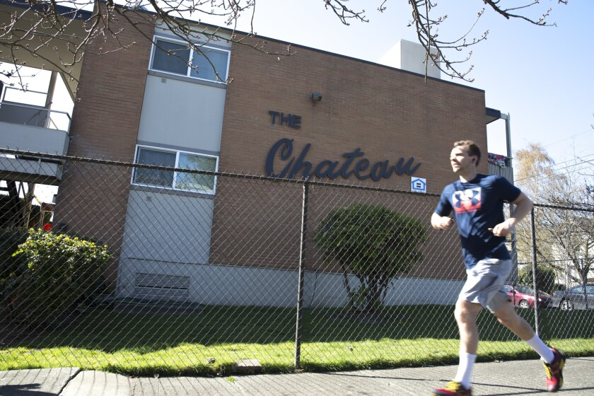 A man jogs by the Chateau apartment building in Seattle's gentrifying Central District. Under the city's new zoning rules, a developer plans to replace the building with five floors of apartments instead of four, and must include low-income units or pay into an affordable-housing fund.