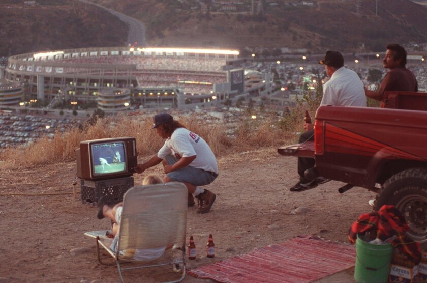 An All-Star view in 1992: Marvin Dupre adjusts the television set as Sheila Dupre (in chair), Robert Bodie and Pancho Villa (far right) watch the All-Star Game from a hill above San Diego Jack Murphy Stadium.