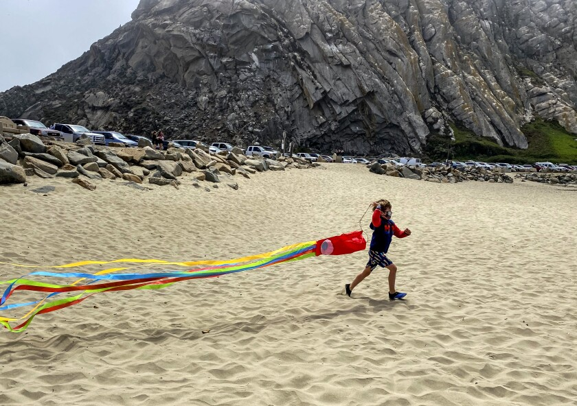 A young visitor attempts to launch a kite on Morro Rock Beach.