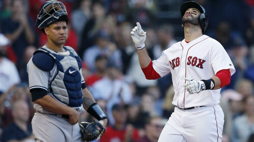 The Yankees' Gary Sanchez, left, watches as the Red Sox's J.D. Martinez celebrates his three-run home run during the fourth inning of a baseball game in Boston, Sunday, Sept. 30, 2018.