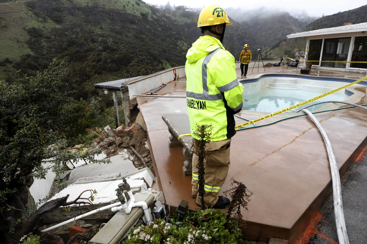 L.A. firefighters oversee drainage of a pool in the yard of a Hollywood Hills home. The pool was compromised as soil shifted during the recent rains.