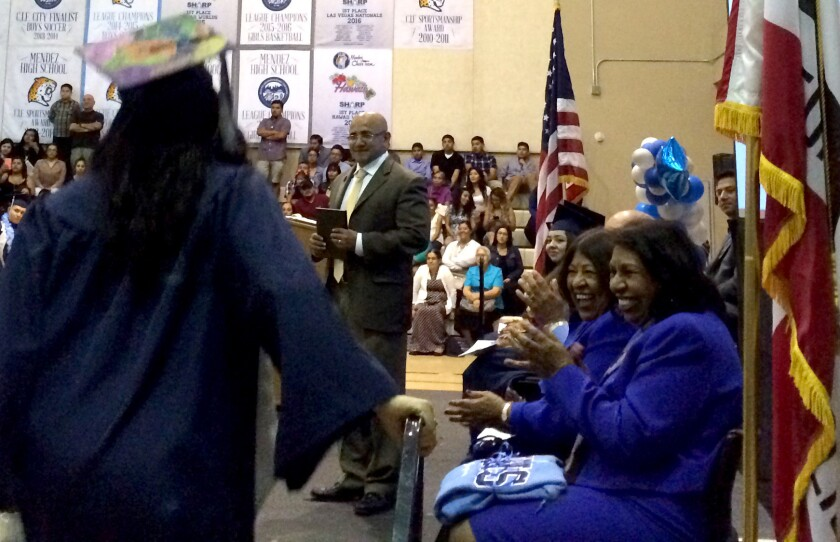 Sylvia Mendez, right, applauds graduates as they receive their diplomas at the Mendez High School graduation in June.