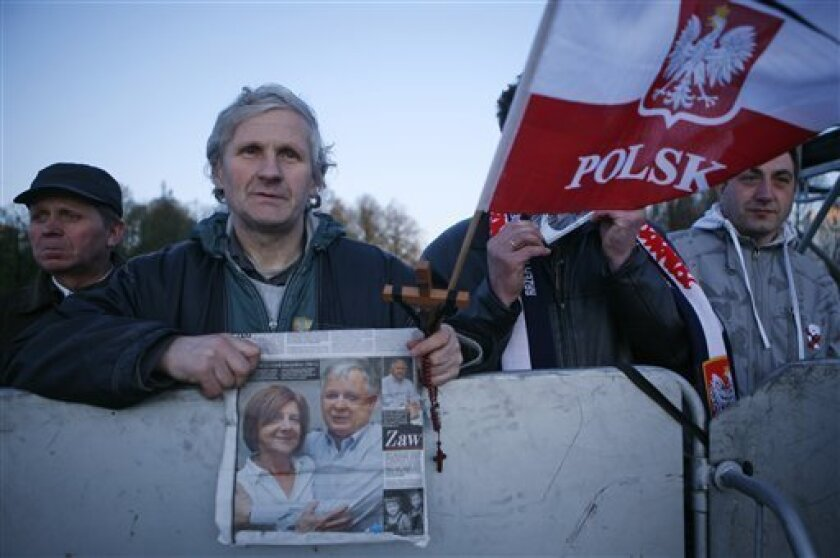 A man holds a cross and a photo of late Polish President Lech Kaczynski as he waits for the beginning of a national memorial service in Pilsudski Square in Warsaw on Saturday, April 17, 2010  in Warsaw, Poland.  Polish President Lech Kaczynski was killed in a plane crash in Russia last Saturday. (A