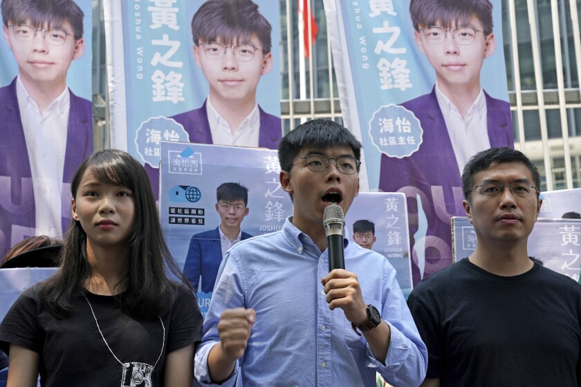Hong Kong democratic activists, Joshua Wong, center, is accompanied with Agnes Chow, left and pro-democracy lawmaker Au Nok-hin, speaks to the media in Hong Kong, Saturday, Sept. 28, 2019. Wong announced plans to contest local elections and warns that any attempt to disqualify him will only spur more support for monthslong pro-democracy protests. (AP Photo/Kin Cheung)