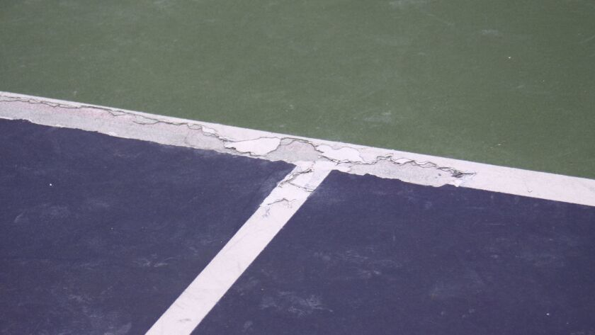 Rain water got between the layers of surfacing material at La Jolla Tennis Club, causing it to chip and create an uneven court.