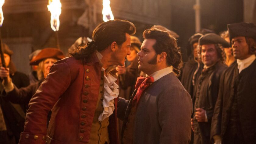 """Luke Evans as Gaston, left, with Josh Gad as LeFou, in """"Beauty and the Beast."""""""