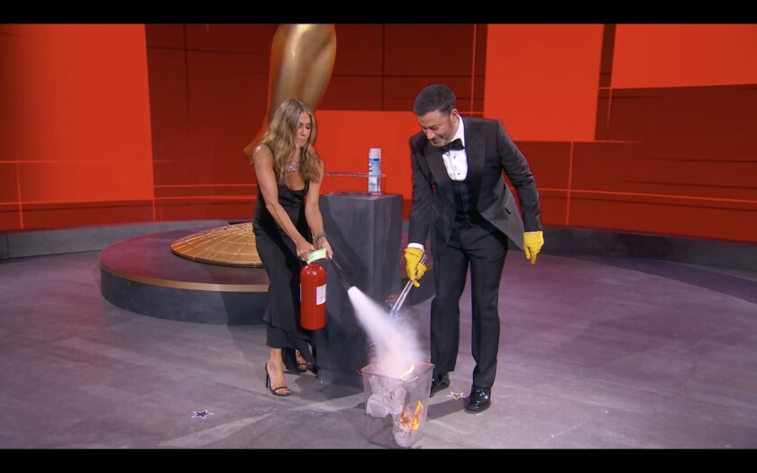 Jennifer Aniston douses a trash can fire at the 2020 Emmys as Jimmy Kimmel uses tongs to grab an envelope from the flames.