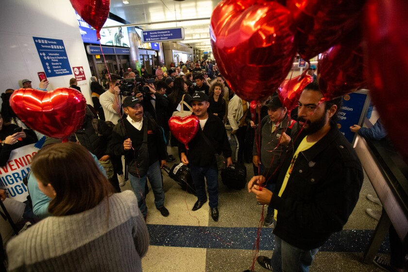 Family members and friends wait at LAX for reunions