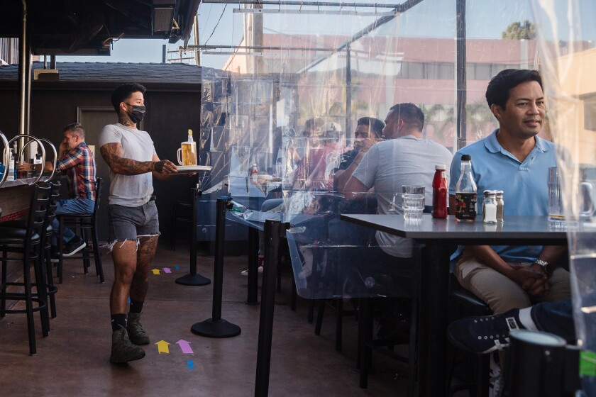 Customers sit at tables that are divided with clear plastic shower curtains at Urban MO's Bar & Grill on July 2.