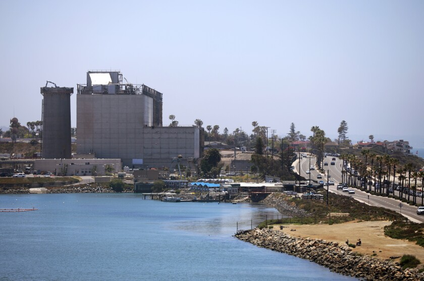 Demolition proceeds on the Encina power plant in Carlsbad, where the 400-foot smokestack is almost gone.