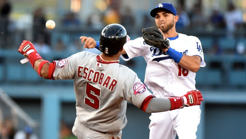 Dodgers second baseman Jose Peraza makes a throw over a sliding Yunel Escobar to complete a double play in the first inning of Monday's game against the Nationals.