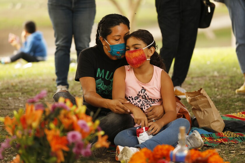 A woman holds her daughter as they both sit on the ground while wearing masks