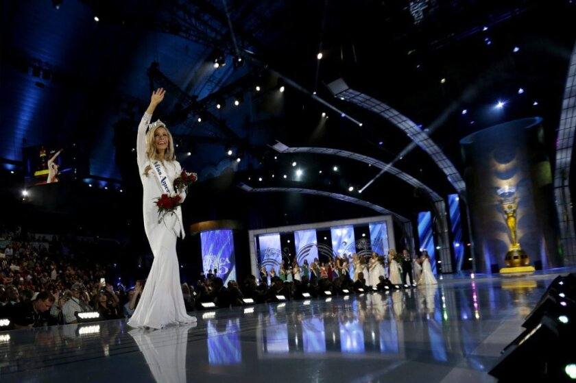Miss America 2015, New York's Kira Kazantsev, waves to the crowd after getting her crown. Domestic violence questions and answers figured front and center in the competition.
