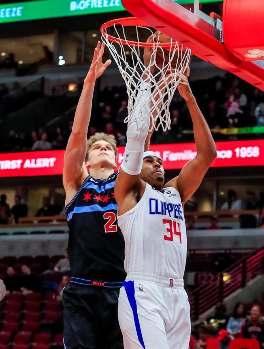 El jugador de los Angeles Clippers Tobias Harris (d) intenta encestar durante un partido. EFE/Archivo
