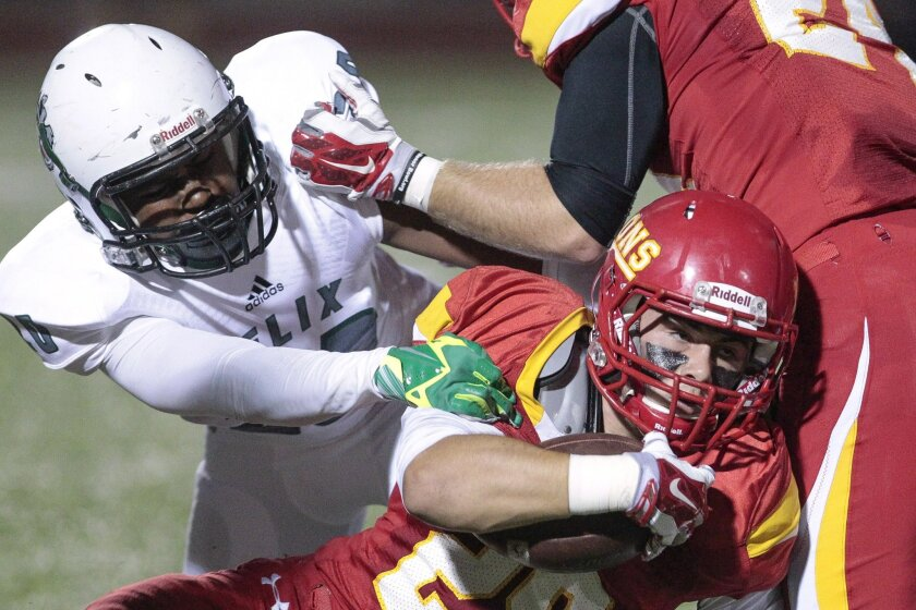 Cathedral Catholic's Hogan Irwin struggles for yardage as Helix defender Tyler Clanton tries to make the stop.