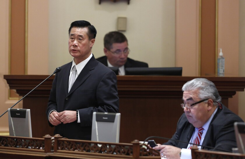 In this Jan. 28 photo, state Sen. Leland Yee (D-San Francisco) speaks on a bill in Sacramento while his colleague, state Sen. Ronald S. Calderon (D-Montebello), works at his desk.