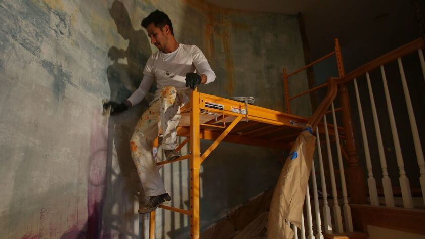 Ceballos works on a mural along the staircase of the Filasky home in La Costa.