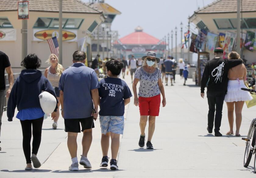 People wearing face masks walk on the Huntington Beach Pier during the coronavirus pandemic.
