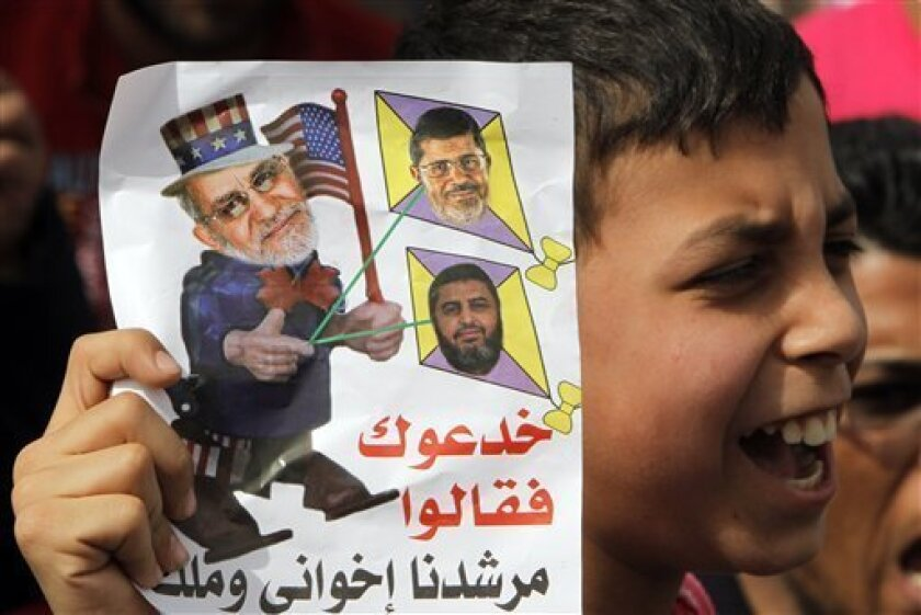 An Egyptian boy holds a cartoon criticizing Muslim Brotherhood Supreme Leader Mohammed Badie, left, Egyptian President Mohammed Morsi, top right, and Muslim Brotherhood deputy leader Khairat el-Shater during anti-Muslim brotherhood protest, in Cairo, Egypt, Friday, March 15, 2013. Hundreds of suppo