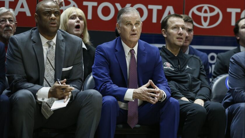 SDSU assistant coaches Rod Palmer (left) sits on the Aztecs bench with Brian Dutcher (center) and Mark Fisher during a game last season.
