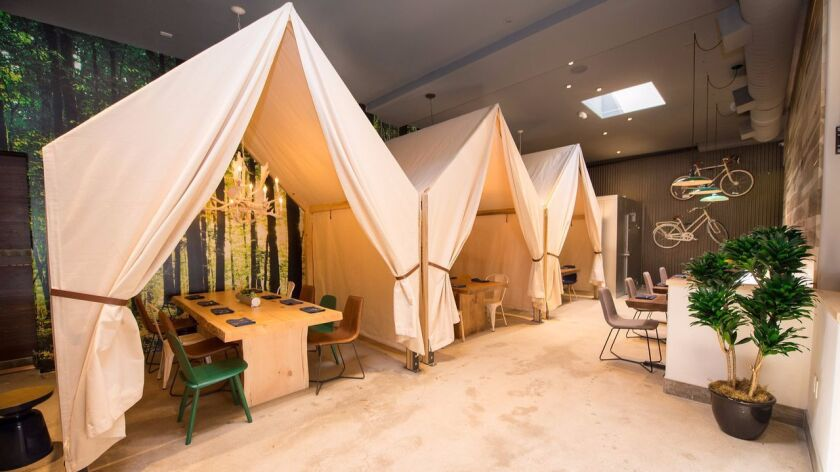Tented tables, bicycles and a forest photo-mural create a campground theme at One Door North in North Park.