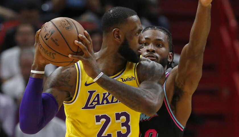 Lakers forward LeBron James looks to pass against Heat forward Justise Winslow in the first quarter Sunday.
