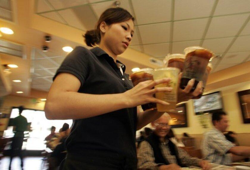 Waitress Sharon Situ hurries an order of drinks at Tasty Garden.