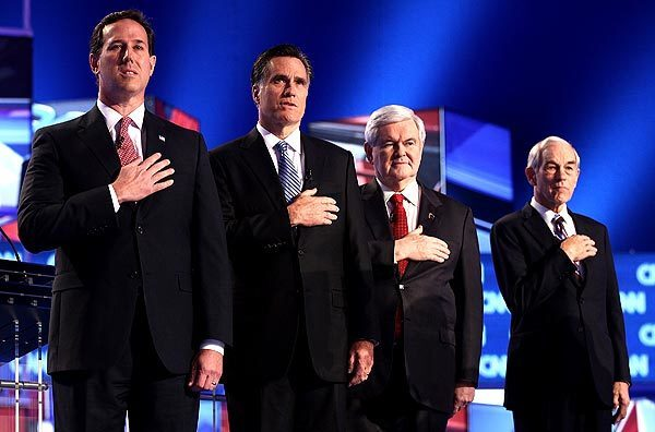 Republican presidential candidates, from left, former U.S. Sen. Rick Santorum, former Speaker of the House Newt Gingrich, former Massachusetts Gov. Mitt Romney and U.S. Rep. Ron Paul of Texas place their hands over their hearts as the national anthem is played before the start of the debate at the North Charleston Coliseum.