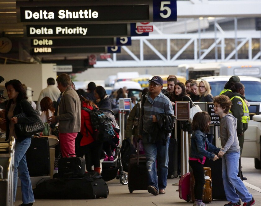 Passengers line up outside LAX Terminal 5 on Wednesday as flight delays and bad weather on the East Coast threatened to disrupt travel plans.