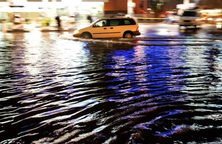 A minivan passed through the flooded intersection of Midway Drive and Rosecrans Street in San Diego last night, one of several waterlogged roadways around the county.