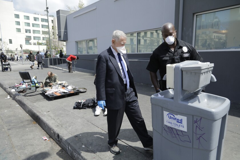 U.S. District Judge David O. Carter and LAPD officer Deon Joseph check an empty hand-washing dispenser while touring skid row last week.