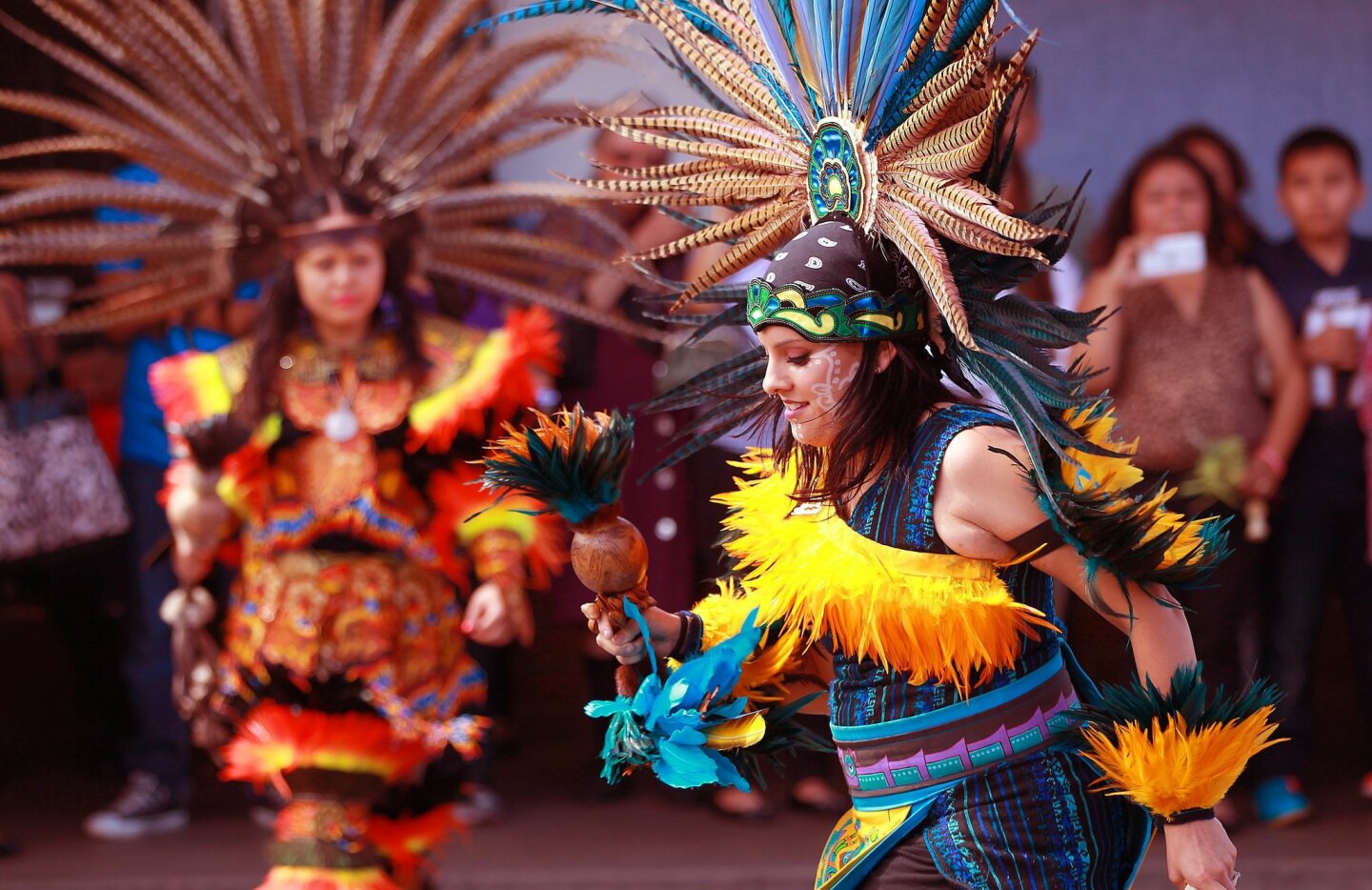 Gloria Delgado, a dancer with Danza Azteca Calpulli Mexihca performs in a courtyard behind Our Lady of Guadalupe Church in Barrio Logan on Palm Sunday.
