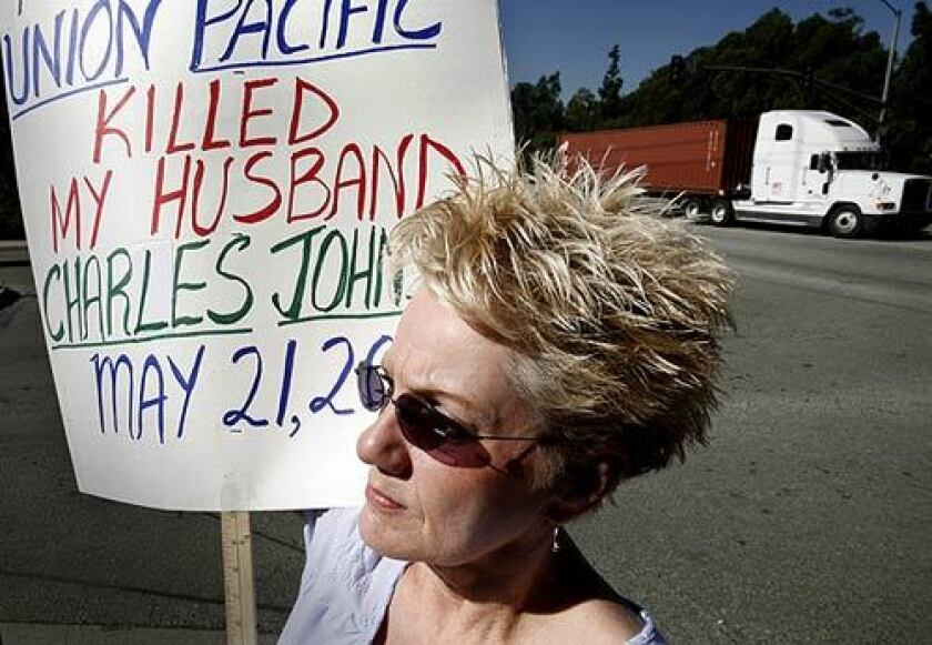 Pat Johnson carries a sign outside the Union Pacific rail yard in Wilmington. Pat's husband, Chuck, a Union Pacific employee, had a heart attack and fell from a platform in 2007. He died on the asphalt. Johnson believes something else went wrong.