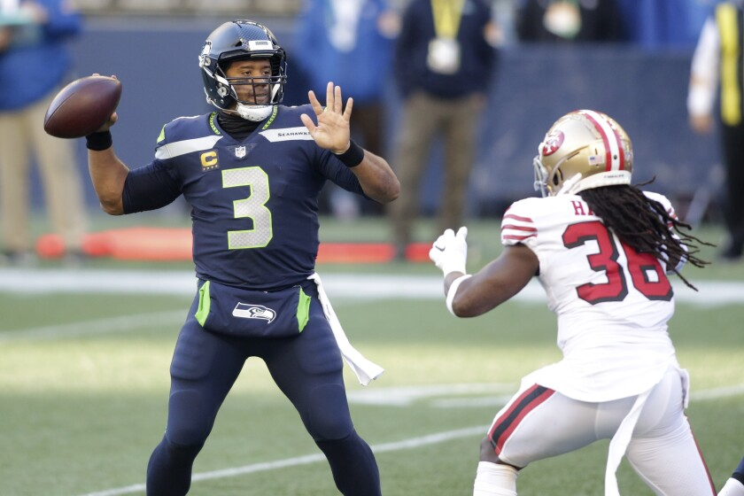 Seattle Seahawks quarterback Russell Wilson (3) makes a touchdown pass to wide receiver DK Metcalf (not shown) as San Francisco 49ers safety Marcell Harris, right, pressures during the first half of an NFL football game, Sunday, Nov. 1, 2020, in Seattle. (AP Photo/Scott Eklund)
