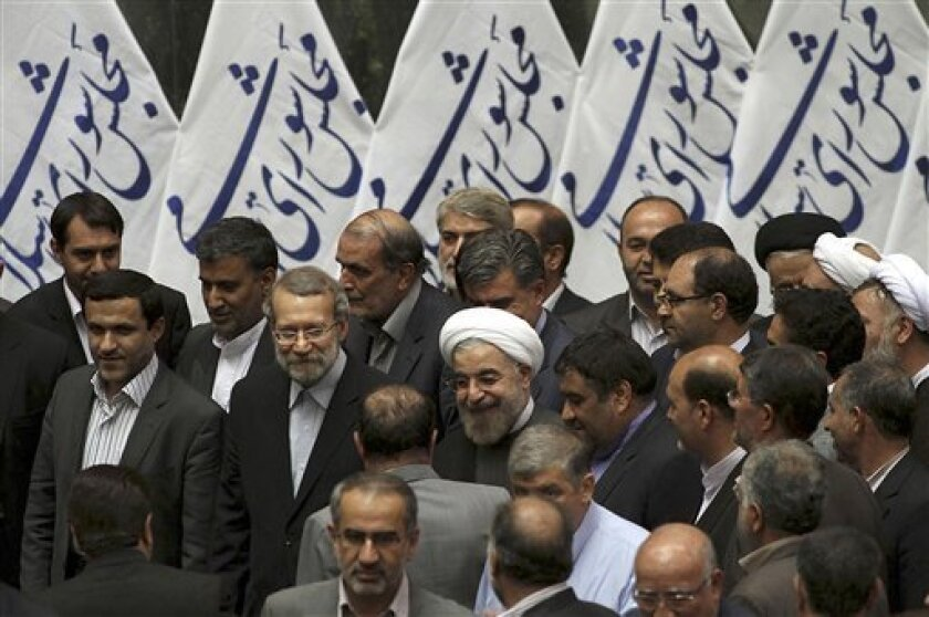 In this Sunday, July 14, 2013 photo released by the official website of the office of Iranian President-elect Hasan Rouhani, Rouhani, center, arrives for a meeting with lawmakers at the parliament, in Tehran, Iran. The Iranian president's inner circle brings more than new names to the Islamic Republic's power structures _ the group of advisers and allies also carries an array of degrees from Western universities. Few doubt that Hasan Rouhani will bring a far calmer and more measured approach tha