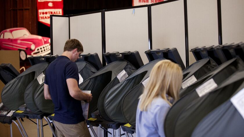 COSTA MESA, JUNE 2, 2014 - Valters Lauzums, left, and Karen Hernadez cast their ballots at Mariners