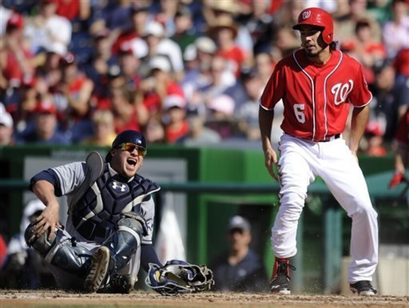 San Diego Padres catcher Yasmani Grandal, left, reacts after he was injured on a play at home as Washington Nationals' Anthony Rendon (6), who was out on the play, looks on during the third inning of a baseball game on Saturday, July 6, 2013, in Washington. The Nationals won 5-4. (AP Photo/Nick Wass)