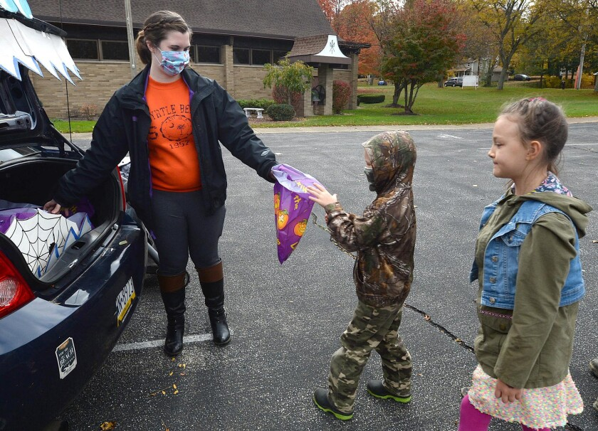 Samantha Ruiz-Bueno, left, passes out candy to Boaz Pettis, 6, of Millcreek Township, Pa., and his sister Callista Pettis, 8, during the Drive-thru Trunk or Treat event for kids at the Fairview United Methodist Church, Saturday, Oct. 31, 2020, in Fairview, Pa. (Jack Hanrahan/Erie Times-News via AP)