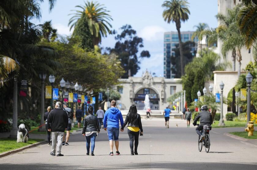 People walk and bike along El Prado at Balboa Park on March 24, 2020.