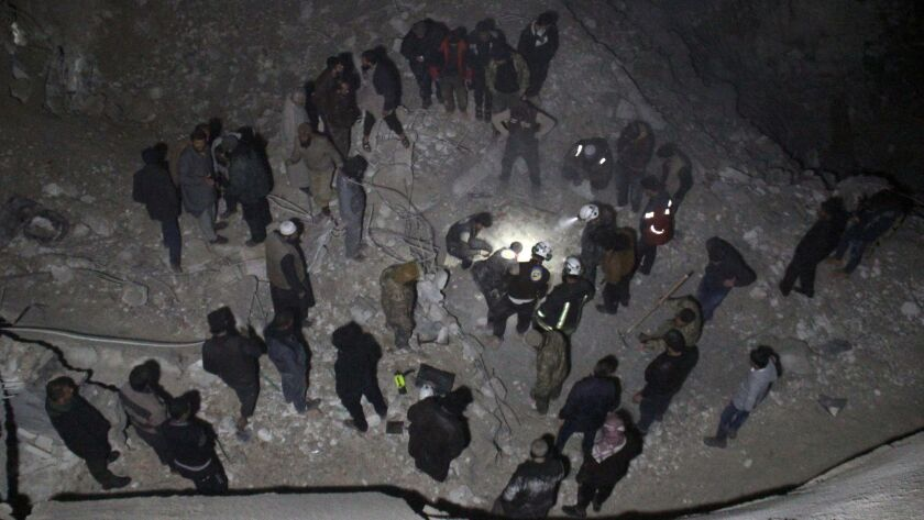 Syrian civil defense volunteers dig through the rubble of a mosque following a reported airstrike there late Thursday.