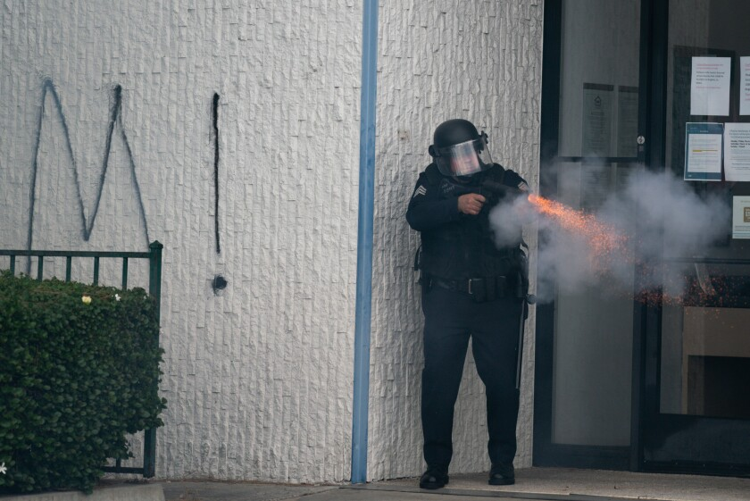 A law enforcement officer discharges a weapon in the Fairfax District on May 30.