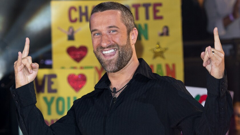 "Dustin Diamond smiling and making a ""rock on"" gesture with his hands"