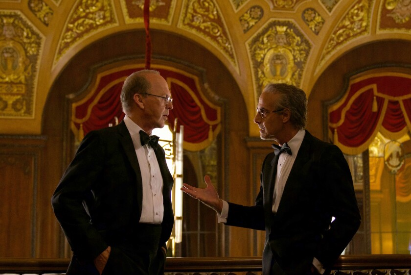 "Two men in formal wear talk in the movie ""Worth."""