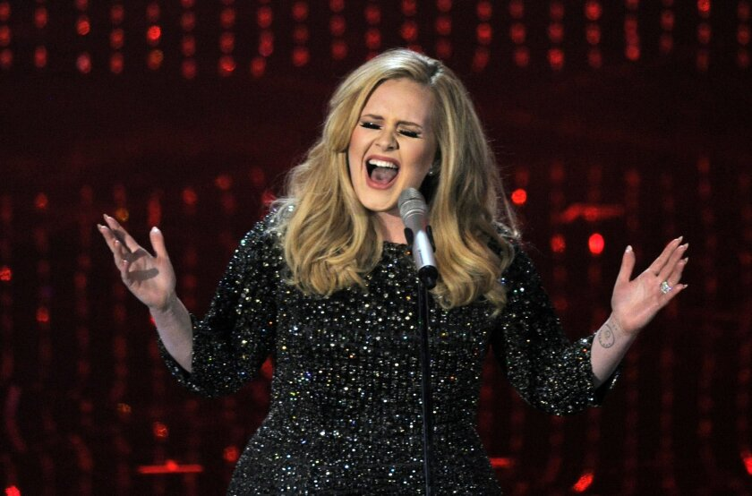 "FILE - In this Feb. 24, 2013 file photo, Adele performs during the Oscars at the Dolby Theatre in Los Angeles. Adele's ""Hello"" single has become the first song to sell one million tracks in a week. Her comeback track sold 1.11 million digital songs, setting a new record. Her complete album ""25,"" wi"