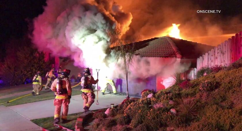 Firefighters battle flames shooting from a garage as smoke billows into the air Tuesday night on Santa Helena in Solana Beach.