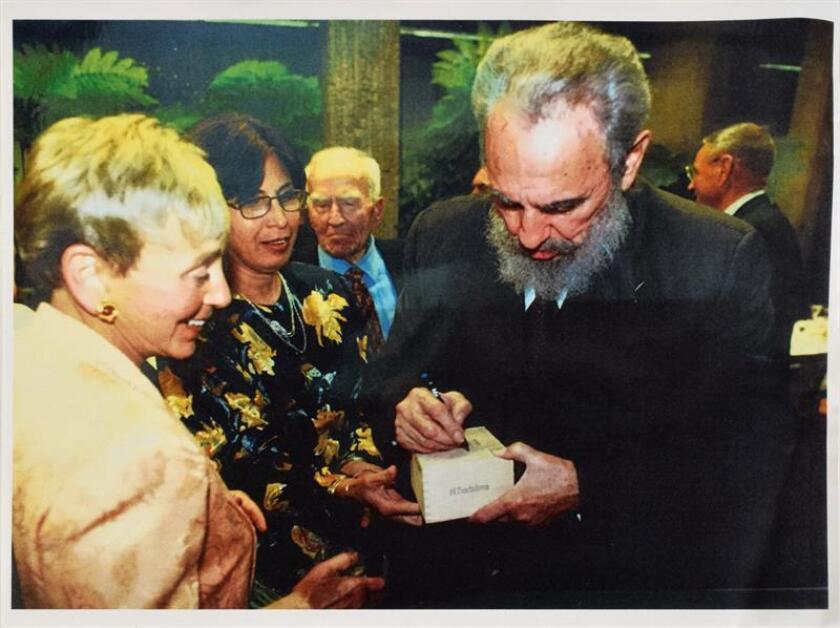 Fotografía cedida por RR Subastas muestra el líder de la revolución cubana Fidel Castro (d) firmando una caja de puros en marzo de 2002 a la activista y filántropa estadounidense de origen húngaro Eva Haller (i). Una caja de puros firmada por el líder de la revolución cubana Fidel Castro fue vendida al mejor postor en Boston (EE.UU.) por 26.950 dólares, informó hoy la casa de subastas estadounidense RR Auction. La caja, que la casa de subastas asegura que formaba parte de la colección personal del dirigente cubano (1926-2016), tiene un tamaño de 21 x 11 x 7,5 centímetros, contiene 24 cigarros del tipo Fundadores de la marca Trinidad y todavía mantiene el sello de garantía de procedencia para tabacos torcidos y picadura cubanos. EFE/RR Auction/SOLO USO EDITORIAL/NO VENTAS
