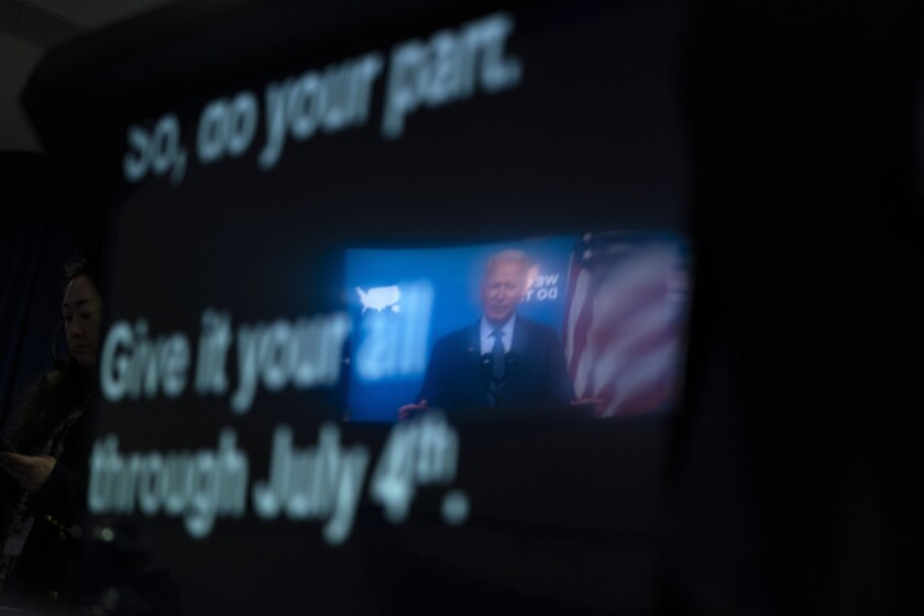 President Biden is reflected in a teleprompter.